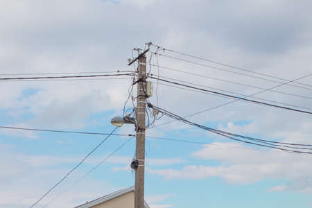 Electric pole with wires and a lantern against the blue sky. The concept of electricity, energy supply.