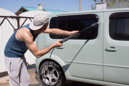 Young man washes a car with water under pressure in the courtyard of the house.