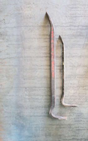 iron nail puller on a rough metal background in style. male locksmith tool. Top view. Mock up. Flat lay composition.