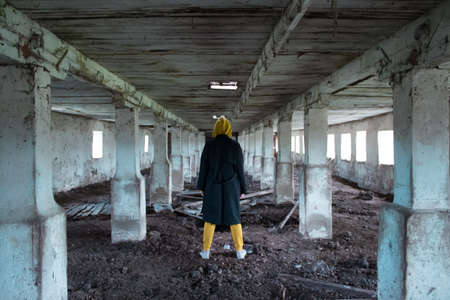 A girl in a gloomy abandoned building in a black cloak. Young woman in an industrial abandoned factory. Archivio Fotografico