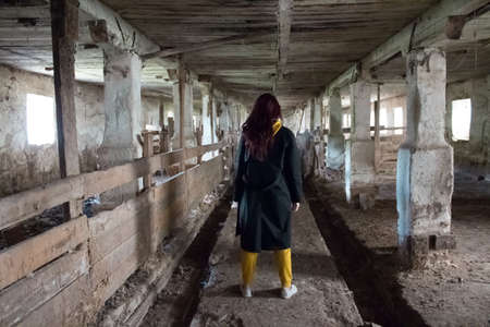A girl in a gloomy abandoned building in a black cloak. Young woman in an industrial abandoned factory.