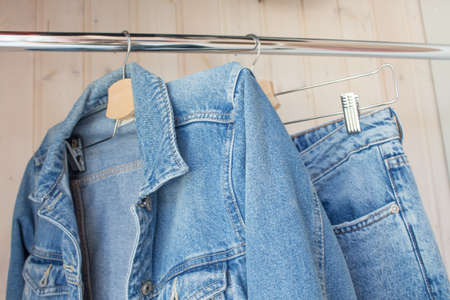 Jeans and jeans on a hanger. Fashionable denim outfit in blue wardrobe. Spring-summer collection, current jeans models.