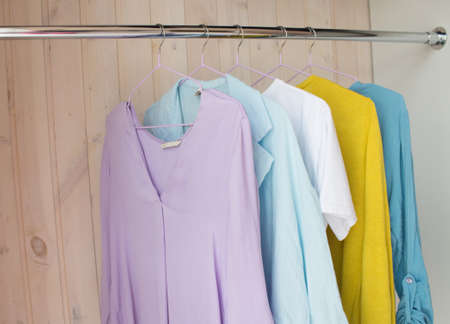 clothes of pastel shades on hangers. analysis of the wardrobe