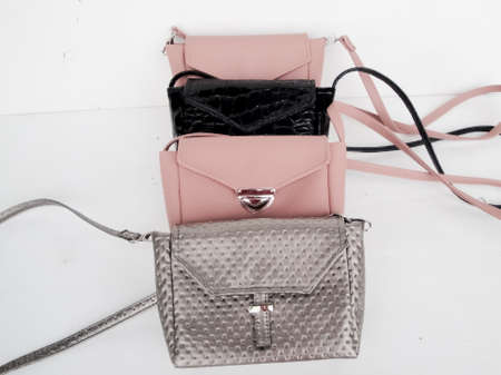 Set of fashionable bags of small and large sizes, pastel colors, black, metallic. Handmade bags on a white background