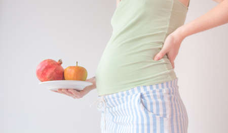 Pregnant woman is holding a bowl of fruit. Pregnant healthy food concept. Vitamins in fruits for pregnant women, a balanced diet, only fresh and healthy food.