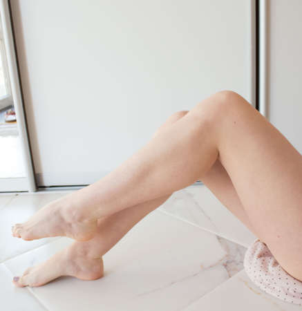 Beautiful female long legs with smooth skin after depilation. A young girl epilated her legs, her skin is silky. Body hair removal, laser hair removal, wax hair removal, shugaring.