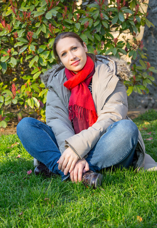 red scarf: woman sitting on the grass in red scarf