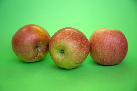 Three red apples on a green background