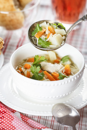 Submission chicken soup with noodles, potatoes and carrot in a white chalice on a tablecloth into a cell