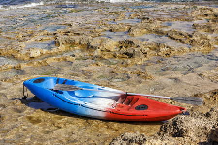 Boat in blue - white and red colors with oars is worth on a rocky beach near the sea