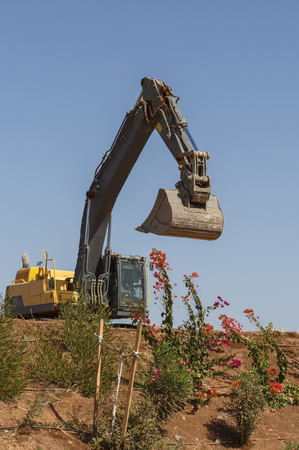 Yellow excavator with raised bucket stands on a hill.