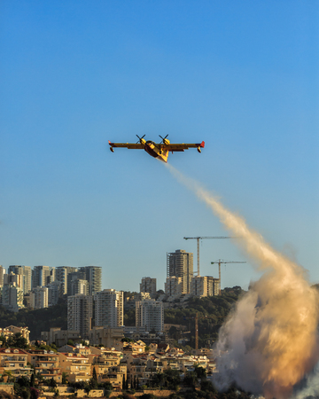 Firefighter planes dropped foam on the burning city Stock Photo