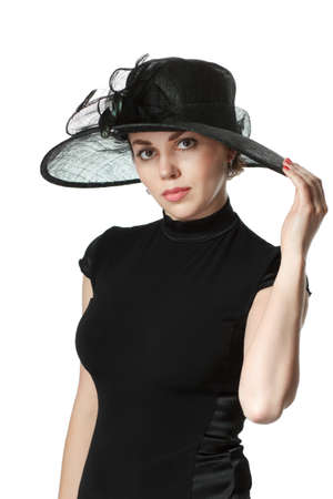 womanhood: Portrait of a beautiful woman in a black dress and hat standing and holding a hat isolated on white background