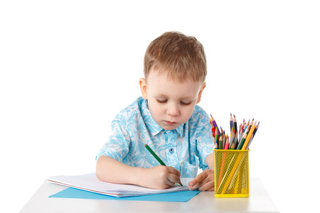diligent: Diligent little boy draws with crayons isolated on white background Stock Photo