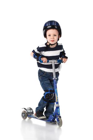 scooter: Ni�o peque�o en la protecci�n del casco y en los volantes de la rodilla y el brazo montado en su moto aislado en fondo blanco