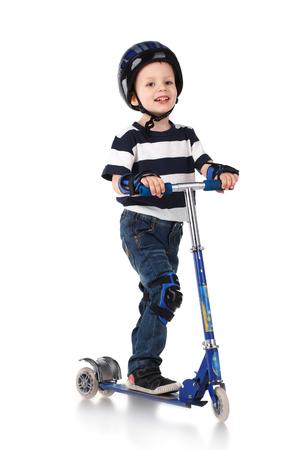 scooter: Ni�o peque�o en la protecci�n del casco y en los volantes de la rodilla y el brazo montado en su moto