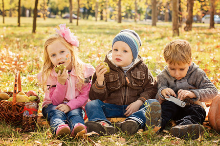 Three happy children playing in autumn park with fruits photo