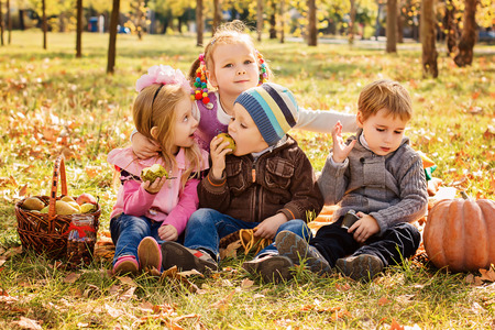 Four happy children playing in autumn park with fruits photo