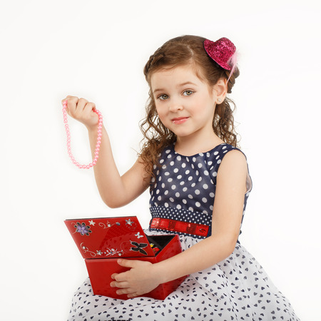 admires: little girl admires the accessories in the box isolated on white background