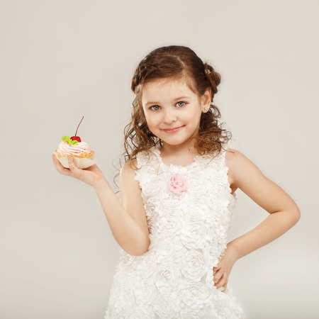 Beautiful little girl holding a delicious appetizing cake with cherry photo