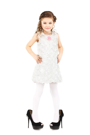 kids wear: Little girl dressed big mothers shoes isolated on white background
