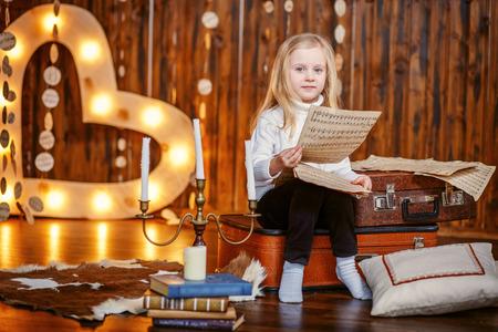 Blonde little girl holding a note in vintage interior Foto de archivo