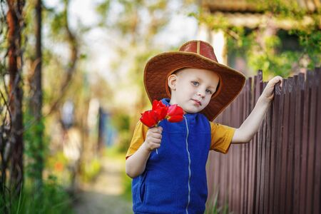 congenial: Portrait of a little boy standing in a big hat with a bouquet of tulips at the wooden fence in the countryside Stock Photo