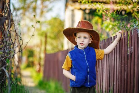 congenial: Portrait of a little boy standing in a big hat in the wooden fence in the countryside Stock Photo