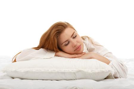 dormir: Muchacha hermosa joven que duerme en la cama abrazando una almohada sobre su estómago. Sueño saludable. Aislado en el fondo blanco.