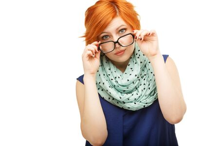 poor eyesight: Portrait of surprised red-haired young woman holding glasses on her nose isolated on white background