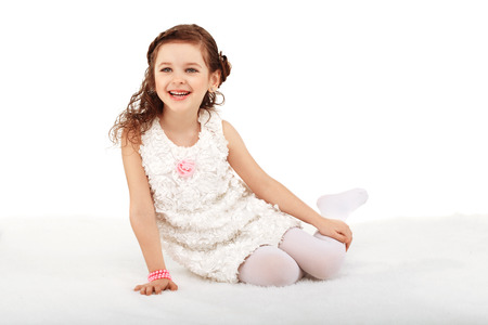 Portrait of a pretty little fun fashion girl sitting on a fluffy rug on the floor and having fun against white background