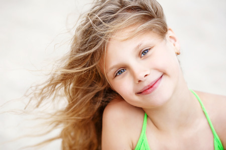 Close-up Portrait of a pretty little girl with waving in the wind long hair sitting on the beach