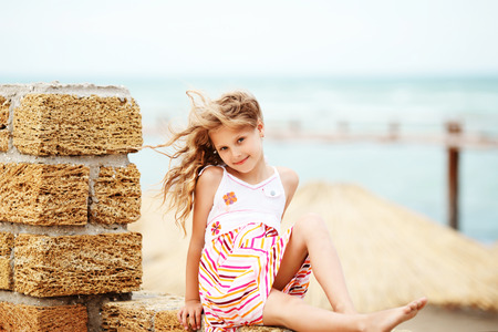 Portrait of a pretty little girl with waving in the wind long hair sitting on the beach Stock Photo