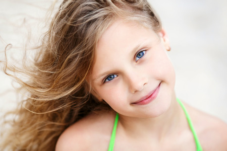 little girl posing: Close-up Portrait of a pretty smiling little girl with waving in the wind long hair sitting on the beach Stock Photo