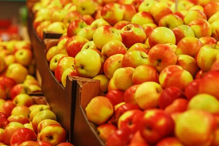 green vegetables: Many ripe yellow-red apples in boxes in the market