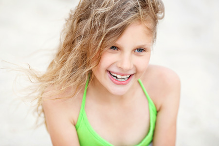 Close-up Portrait of a pretty smiling little girl with waving in the wind long hair sitting on the beach Stock Photo