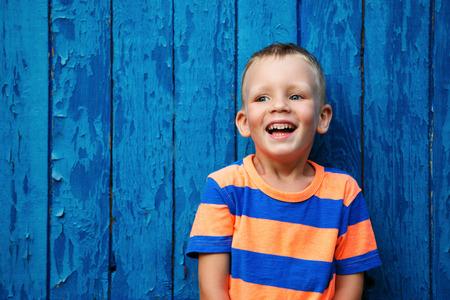 Portrait of happy joyful beautiful little boy against the old textured blue wall