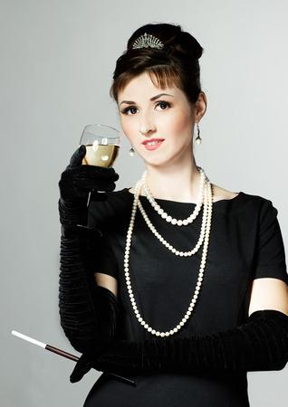 Portret van een mooie jonge vrouw in retro stijl met sigaret in mondstuk in het beeld van de beroemde actrice