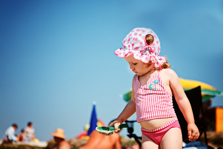 children swimsuit: Cute little girl playing on the beach