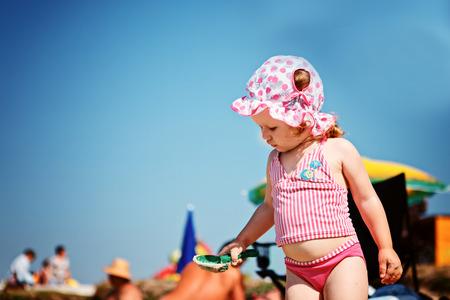 traje de bano: Ni�a linda que juega en la playa Foto de archivo