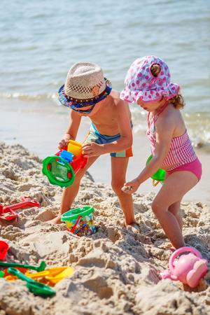 children swimsuit: Cute little boy and girl playing on the beach Stock Photo