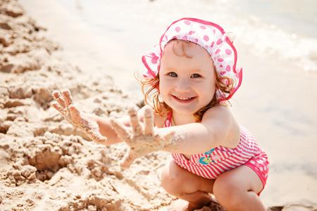 little finger: Cute little girl playing on the beach