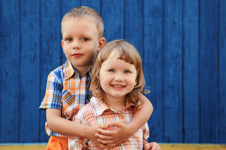 honey blonde: Portrait of happy joyful beautiful little boy and girl against the old textured blue wall Stock Photo