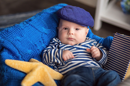 striped vest: Portrait of a cute little boy in a striped vest and cap in the interior with sea style Stock Photo