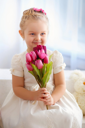 child s: beautiful little girl in a white dress sitting on a windowsill with a bouquet of pink tulips Stock Photo