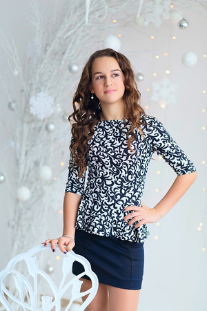 teen girl: Portrait of a pretty teen girl with flowing long curly hair in interior with Christmas decorations