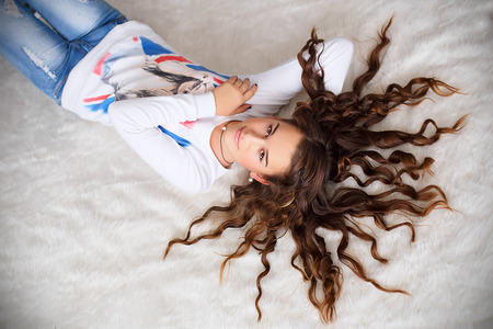 teen girl: Portrait of a pretty teen girl lying on the floor with her long hair wavy