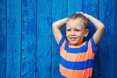 honey blonde: Portrait of happy joyful beautiful little boy against the old textured blue wall