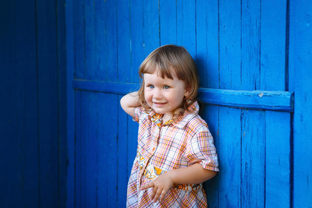 honey blonde: Portrait of happy joyful beautiful little girl against the old textured blue wall Stock Photo