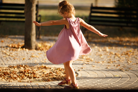leaves: Full length portrait of a little girl dancing in the park a warm autumn evening. In move. Back view Stock Photo